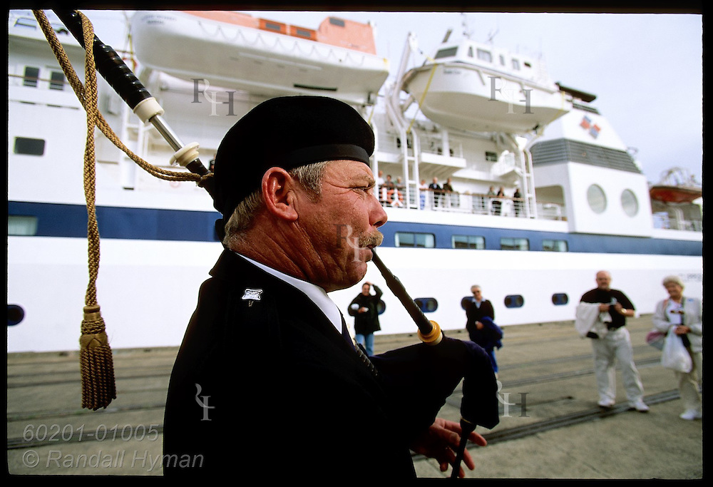 Bagpiper on wharf serenades cruise ship Clipper Odyssey before its departure from Scot-settled town of Dunedin, New Zealand.