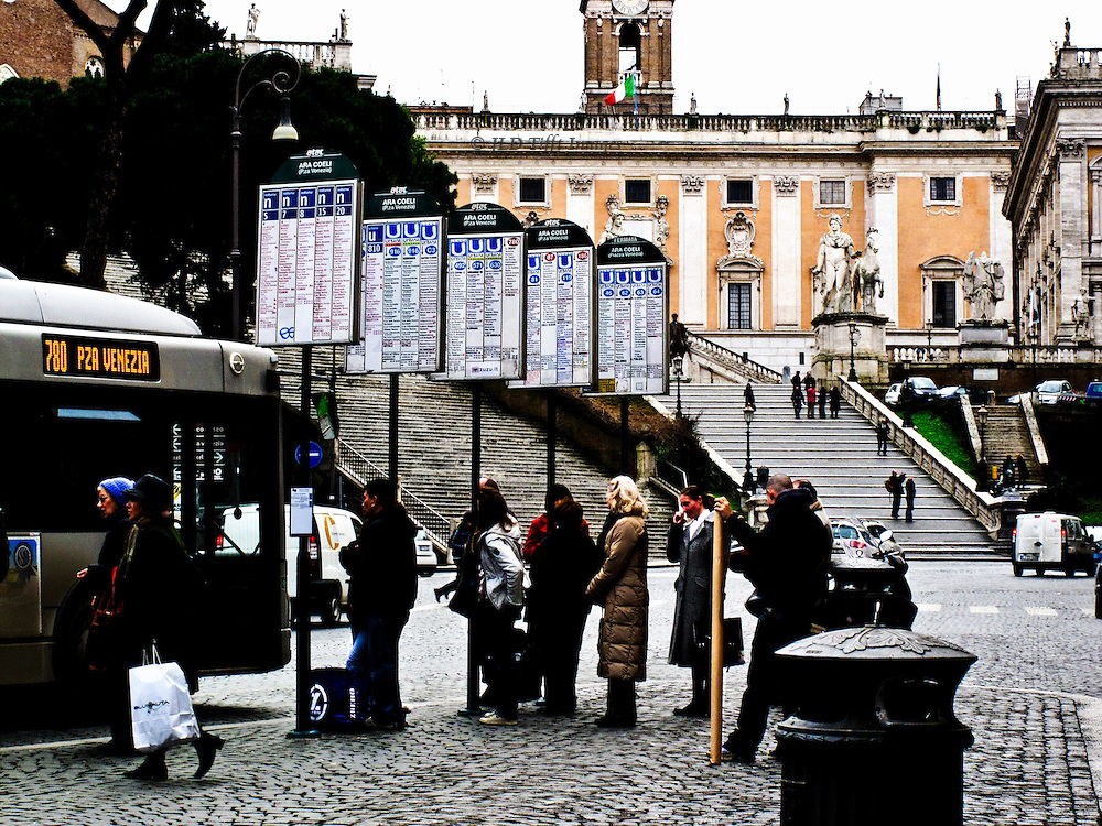 """Bus stop below the Capitoline, showing a row of five route signs, passengers waiting on the sidewalk, and a stopped bus labelled """"Pza. Venezia"""" at the curb."""