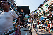 Woman traveling in rickshaw in Kolkata (India).