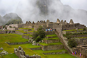 """Visitors explore the """"urban"""" or residential areas of the ancient site of Machu Pichu in the Cusco region of Peru. The residential area is built in the lower regions of the city and housed farmers, servants and teachers etc."""