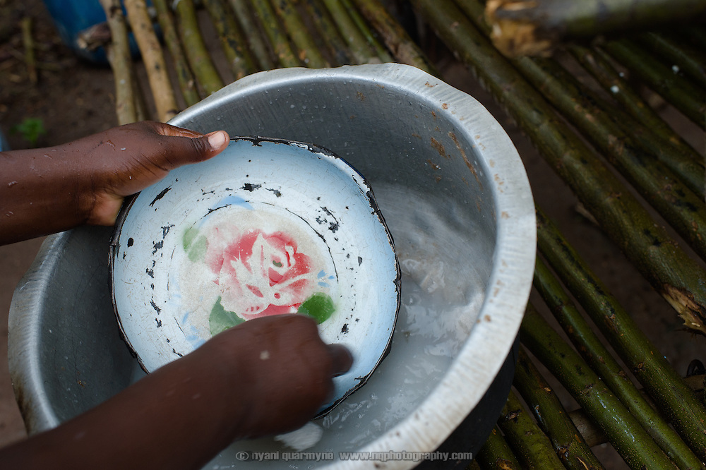 Margaret Kigeni (14), washing the dishes at her home on 1 August 2014, is a student at Achilet Primary School in the Eastern Region of Uganda. She is an Afripads customer, and her school particpates in Menstural Hygiene Management activities.
