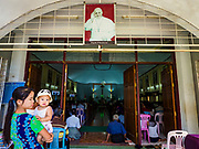19 NOVEMBER 2017 - HWAMBI, YANGON REGION, MYANMAR: A woman comforts her baby during mass at Sacred Heart's Catholic Church in Hwambi, about 90 minutes north of Yangon. A portrait of Pope Francis hangs over the entrance of the church. Catholics in Myanmar are preparing for the visit of Pope Francis. He is coming to the Buddhist majority country November 27-30. There about 500,000 Catholics in Myanmar, about 1% of the population. Catholicism was originally brought to what is now Myanmar more than 500 years ago by Portuguese missionaries and traders.    PHOTO BY JACK KURTZ