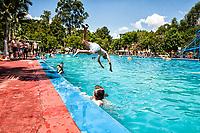 Menino saltando na piscina nas Thermas de Ilha Redonda. Palmitos, Santa Catarina, Brasil. / Boy jumping into the swimming pool at Thermas de Ilha Redonda. Palmitos, Santa Catarina, Brazil.