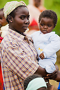 A woman holds her child outside the UNICEF-sponsored Bazzama kindergarden in the town of Bazzama, Cameroon on Wednesday September 16, 2009.  The school integrates the children of refugees from Central African Republic with residents from the area.