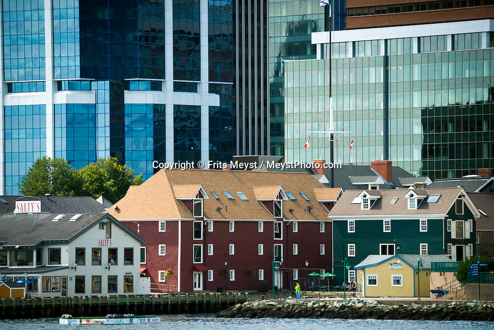 """Halifax, Nova Scotia, Canada, August 2014. Walk the ocean's edge along the historic Halifax waterfront. Start at Pier 21 – the gateway into Canada for one million immigrants – and then explore eclectic shops, some of the city's best restaurants, and ships including the last of the WWII convoy escort corvettes.<br /> <br /> Discover the oldest continuously operating farmers' market in North America, and exhibits at the Maritime Museum of the Atlantic including displays on the city's link to the Titanic disaster. End at the timber-frame & stone warehouses of Historic Properties – originally built to safeguard booty captured by legalized pirates called privateers. Nova Scotia was one of the original four provinces that became part of Canada in 1867.  """"Nova Scotia"""" is Latin for """"New Scotland"""", and Scottish settlers brought culture and traditions that continue to this day. Photo by Frits Meyst / MeystPhoto.com"""