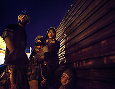 Women with children try to climb the border