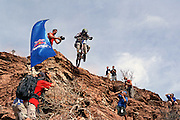 Photographers scramble to get a shot of Andrew Shandro dropping off a Virgin Utah cliff in the 2002 Red Bull Rampage freeride mountain bike contest