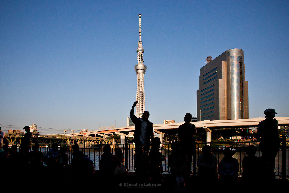 Japan - Tokyo - Sky tree, the hihest bulding of japan and second of Asia,  with a man in the shadow and one arm raised to the tower in the foreground.