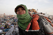 A worker at The Stung Meanchey Landfill in Phnom Penh, Cambodia, shoulders a gaff and a bag filled with recyclable material near the end of the day.