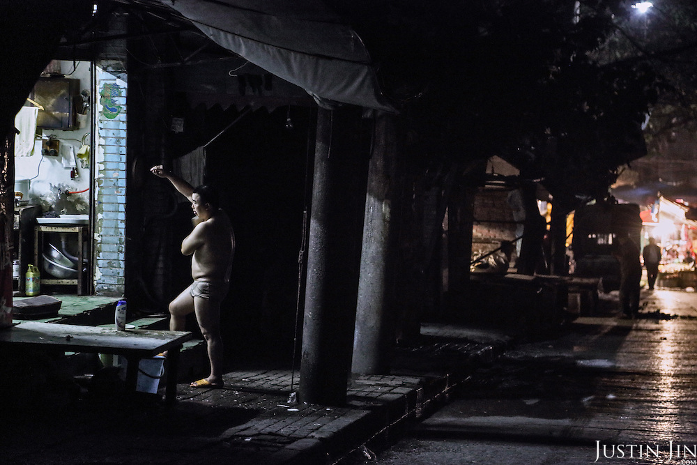 A rural migrant bathes on the street at midnight in the southwestern Chinese megapolis of Chongqing.<br /> <br /> Migrants often work through the nights. For many, this is a long and arduous step in the transition from farming to urban living. <br /> <br /> China is hoping by relocating farmers into cities they would start to buy food, making a break from the cycle of farmers consuming only what they produce.<br /> <br /> China is pushing ahead with a dramatic, history-making plan to move 100 million rural residents into towns and cities between 2014 and 2020 &mdash; but without a clear idea of how to pay for the gargantuan undertaking or whether the farmers involved want to move.<br /> <br /> Moving farmers to urban areas is touted as a way of changing China&rsquo;s economic structure, with growth based on domestic demand for products instead of exporting them. In theory, new urbanites mean vast new opportunities for construction firms, public transportation, utilities and appliance makers.