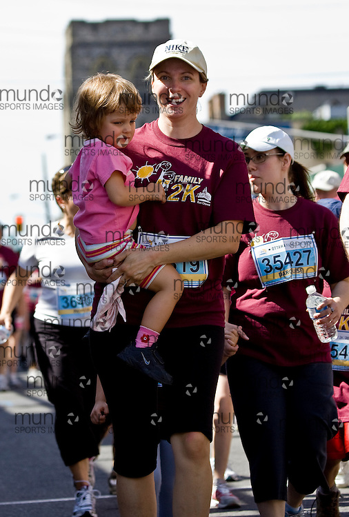 (Ottawa, ON --- May 29, 2010) A mom carries her daughter through the 2km kids race during the Ottawa Race Weekend. Photograph copyright Sean Burges / Mundo Sport Images