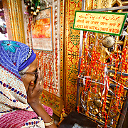 A woman finishes her prayers by taking the blessing of God and putting it on her face. Typical of the ending of any Islamic prayer. This lady stands outside the tomb of Nizzamudin New Delhi. Women are typically not allowed inside the room with the tomb.