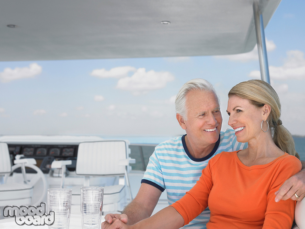 Smiling middle-aged couple on yacht