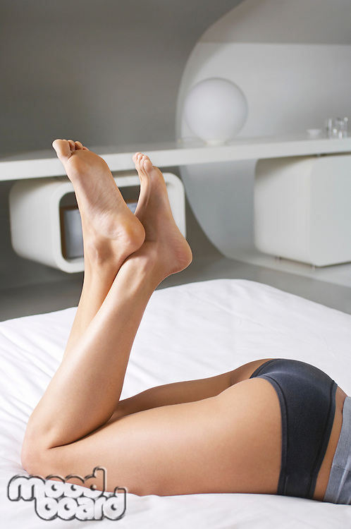 Young woman lying on bed low section side view