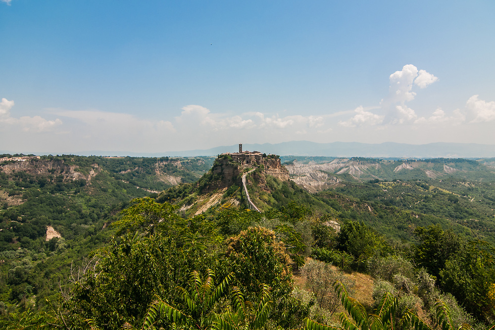 A view of the village of Civita di Bagnoregio.<br /> Civita di Bagnoregio is a town in the Province of Viterbo in central Italy, a suburb of the comune of Bagnoregio, 1 kilometre (0.6 mi) east from it. It is about 120 kilometres (75 mi) north of Rome. Civita was founded by Etruscans more than 2,500 years ago. Bagnoregio continues as a small but prosperous town, while Civita became known in Italian as La citt&agrave; che muore (&quot;The Dying Town&quot;). Civita has only recently been experiencing a tourist revival. The population today varies from about 7 people in winter to more than 100 in summer.The town was placed on the World Monuments Fund's 2006 Watch List of the 100 Most Endangered Sites, because of threats it faces from erosion and unregulated tourism.