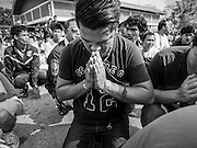 "07 MARCH 2015 - NAKHON CHAI SI, NAKHON PATHOM, THAILAND: A man prays after rushing the stage at the Wat Bang Phra tattoo festival. Wat Bang Phra is the best known ""Sak Yant"" tattoo temple in Thailand. It's located in Nakhon Pathom province, about 40 miles from Bangkok. The tattoos are given with hollow stainless steel needles and are thought to possess magical powers of protection. The tattoos, which are given by Buddhist monks, are popular with soldiers, policeman and gangsters, people who generally live in harm's way. The tattoo must be activated to remain powerful and the annual Wai Khru Ceremony (tattoo festival) at the temple draws thousands of devotees who come to the temple to activate or renew the tattoos. People go into trance like states and then assume the personality of their tattoo, so people with tiger tattoos assume the personality of a tiger, people with monkey tattoos take on the personality of a monkey and so on. In recent years the tattoo festival has become popular with tourists who make the trip to Nakorn Pathom province to see a side of ""exotic"" Thailand.   PHOTO BY JACK KURTZ"