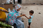 Nafeesa, 27, tends to one of her 4 children while rolling bidis (indian cigarettes) in her house in a slum in Tonk, Rajasthan, India, on 19th June 2012. Nafeesa's health deteriorated from bad birth spacing and over-working. While her husband works far from home, she rolls bidis (indian cigarettes) to make an income and support the family. She single-handedly runs the household and this has taken a toll on her health and financial insufficiencies has affected her children's health. Photo by Suzanne Lee for Save The Children UK