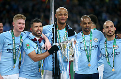 (left to right) Manchester City's Kevin De Bruyne, Sergio Aguero, Vincent Kompany, Luis Fernandinho and David Silva pose with the trophy after winning the Carabao Cup Final