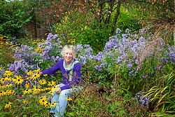 Carol Klein sitting amongst Aster 'Little Carlow' and Rudbeckia fulgida var. deamii AGM