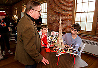 Paul Luff and Isaac Allen listen to Devon Howe describe projects from his engineering class with Huot Technical Center during Maker's Night exhibit at Belknap Mill Thursday evening.     (Karen Bobotas/for the Laconia Daily Sun)
