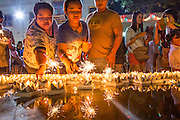 28 NOVEMBER 2012 - BANGKOK, THAILAND: People float their krathongs in a small pool on Loy Krathong at Wat Yannawa in Bangkok. Loy Krathong takes place on the evening of the full moon of the 12th month in the traditional Thai lunar calendar. In the western calendar this usually falls in November. Loy means 'to float', while krathong refers to the usually lotus-shaped container which floats on the water. Traditional krathongs are made of the layers of the trunk of a banana tree or a spider lily plant. Now, many people use krathongs of baked bread which disintegrate in the water and feed the fish. A krathong is decorated with elaborately folded banana leaves, incense sticks, and a candle. A small coin is sometimes included as an offering to the river spirits. On the night of the full moon, Thais launch their krathong on a river, canal or a pond, making a wish as they do so.    PHOTO BY JACK KURTZ