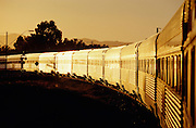 The Ghan glitters in a golden light while leaving Port Augusta at sunrise.