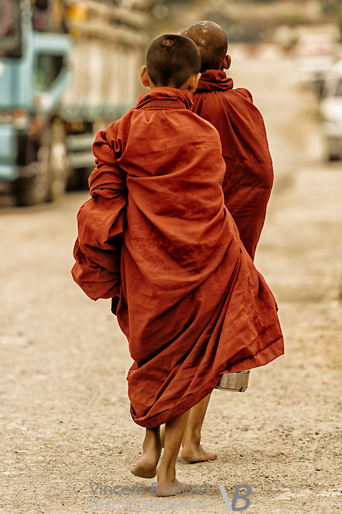 Two young monks walking to get their morning food donation