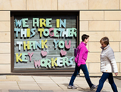 Edinburgh, Scotland, UK. 18 April 2020. Views of empty streets and members of the public outside on another Saturday during the coronavirus lockdown in Edinburgh. Messages of support to NHS in windows of Premier Inn hotel .Iain Masterton/Alamy Live News