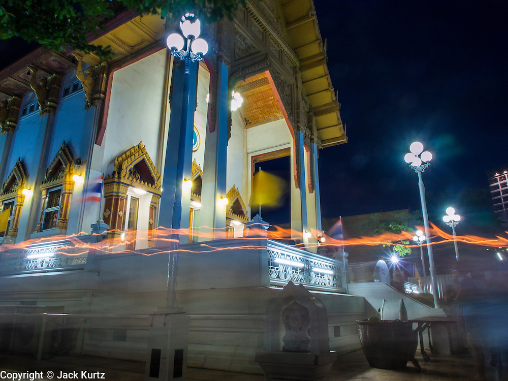"""13 MAY 2013 - BANGKOK, THAILAND:  A time exposure of people carrying candles in a procession for Vesak around Wat That Thong in Bangkok. Vesak, called Wisakha Bucha in Thailand, is one of the most important Buddhist holy days celebrated in Thailand. Sometimes called """"Buddha's Birthday"""", it actually marks the birth, enlightenment (nirvana), and death (Parinirvana) of Gautama Buddha in the Theravada or southern tradition. It is also celebrated in Cambodia, Laos, Myanmar, Sri Lanka and other countries where Theravada Buddhism is the dominant form of Buddhism.    PHOTO BY JACK KURTZ"""
