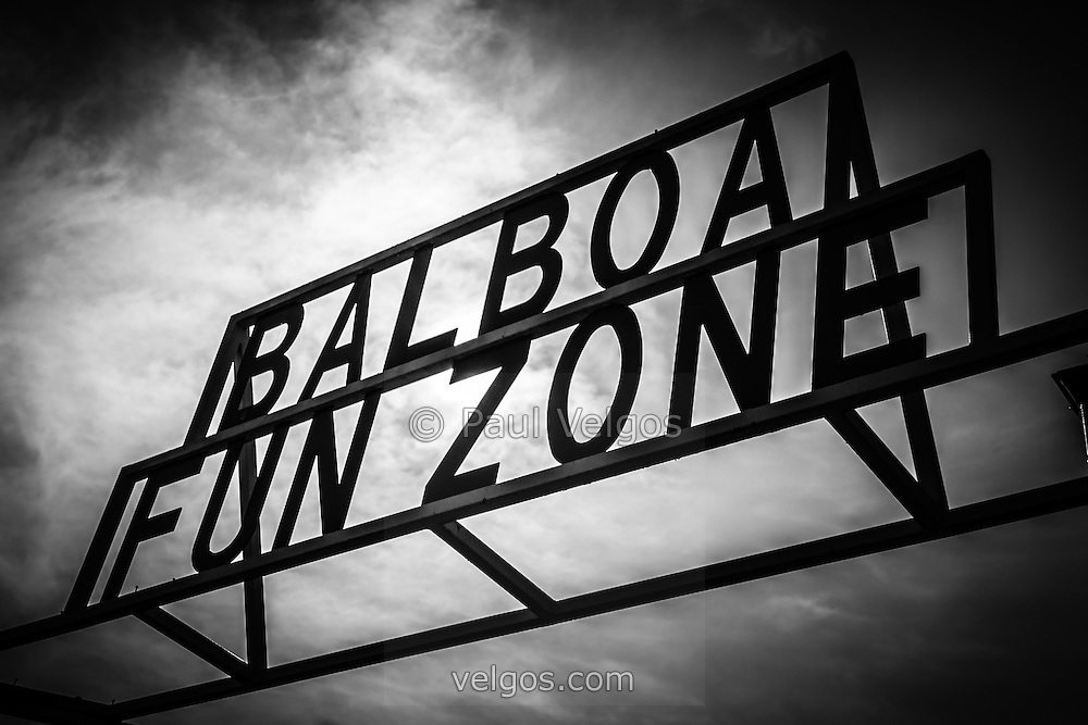 Balboa Fun Zone sign picture in Newport Beach. Photo is black and white with a dramatic sky. The Balboa Fun Zone is a small amusement park built in 1936 on Balboa Peninsula in Newport Beach, Orange County, California. The land was purchased by the Newport Harbor Nautical Museum which has been slowly closing rides to expand its museum.