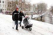 Een man en vrouw lopen met een kinderwagen door de sneeuw over de Oudegracht in Utrecht.<br /> <br /> A man a woman are walking with a stroller at the Oudegracht Utrecht in the snow.