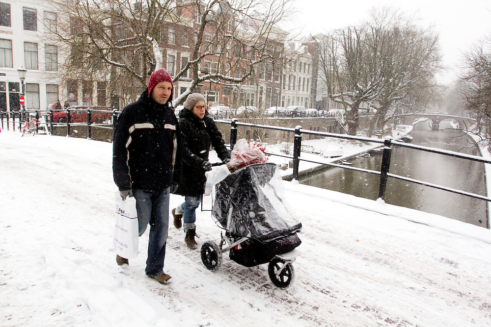 Een man en vrouw lopen met een kinderwagen door de sneeuw over de Oudegracht in Utrecht.<br /> <br /> A man a woman are walking with a stroller at the Oudegracht Utrecht in the snow.
