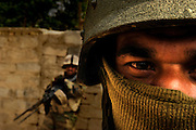 An Iraqi Army soldier covers his face to maintain anonymity within his community during routine foot patrols in New Baqubah, Iraq.
