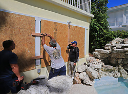 September 6, 2017 - Homestead, Florida, U.S. - From left, JC Abreu, Peter Gonzalez, and Jorge Abreu with Hurricane Busters Enterprises install hurricane shutters at a home in Key Largo in preparation for Hurricane Irma on Wednesday. (Credit Image: © Al Diaz/TNS via ZUMA Wire)