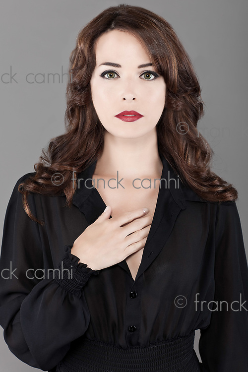 Portrait of sexy Caucasian middle aged woman sexy with beautiful green eyes and red lips isolated on gray background