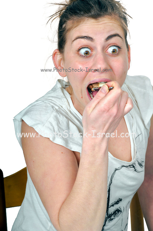 Woman with eyes wide open eats cream cake