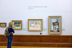 Visitor looking at paintings on display at Kelvingrove Art Gallery and Museum in Glasgow United Kingdom