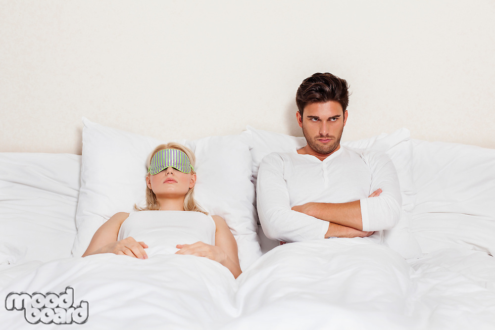 Displeased young man with woman sleeping in bed