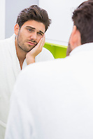 Reflection of frustrated ill man in mirror