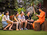 21 NOVEMBER 2015 - BANGKOK, THAILAND: A monk talks to a group of people in a quiet part of Wat Saket at the Wat Saket temple fair. Wat Saket is on a man-made hill in the historic section of Bangkok. The temple has golden spire that is 260 feet high which was the highest point in Bangkok for more than 100 years. The temple construction began in the 1800s in the reign of King Rama III and was completed in the reign of King Rama IV. The annual temple fair is held on the 12th lunar month, for nine days around the November full moon. During the fair a red cloth (reminiscent of a monk's robe) is placed around the Golden Mount while the temple grounds hosts Thai traditional theatre, food stalls and traditional shows.     PHOTO BY JACK KURTZ