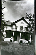 two young boys with bicycle in front of house 1920s