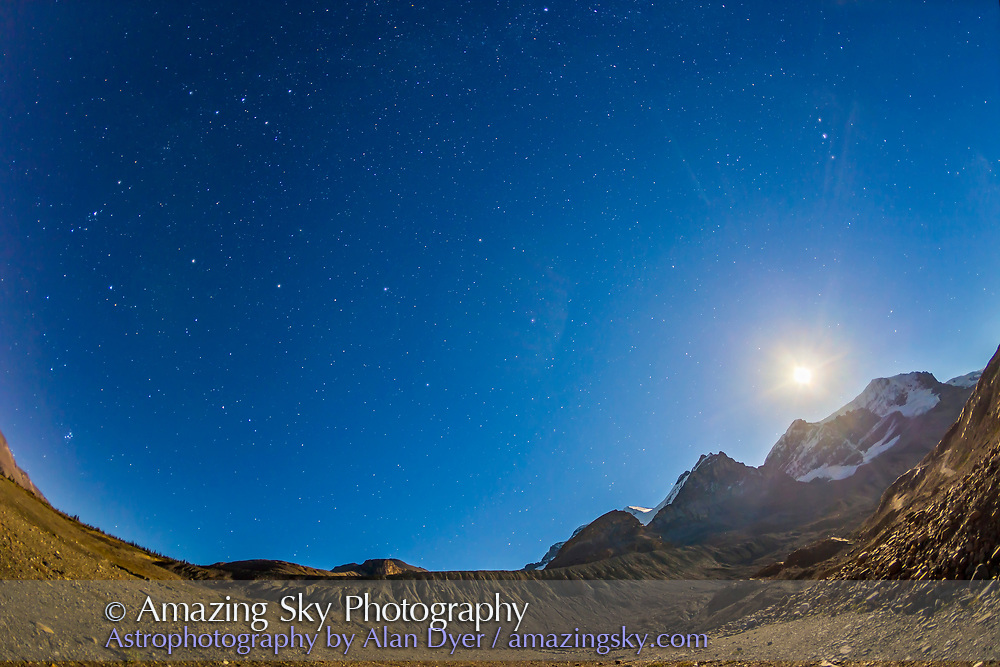 The constellation of Andromeda (the arc of stars at left) and associated autumn constellations over Mt. Andromeda (at right) at the Columbia Icefelds in Jasper National Park, Alberta. The waxing gibbous Moon is over Mt. Andromeda at right. Cassiopeia is at upper left, the Pleiades are rising at lower left. Pegasus is at centre; Perseus is at far left. Altair is at upper right. The Moon adds some lens flares.<br /> <br /> This is an HDR stack of 3 exposures at 1-stop intervals (5s, 10s and 20s) with the Canon 15mm full-frame fish-eye lens at f/2.8 and Canon 6D at ISO 800. Shot from the lower parking lot at Athabasca Glacier.