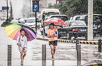 A mother checking that her son is alright as they wait to cross the pedestrian crossing. Notice that the mother is carrying  a smaller umbrella as compared to her son. With the one child policy, the son always get the best treatment in China.