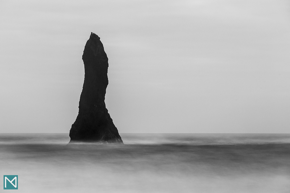 A long exposure turns a rough sea at Reynisfjara beach at mainland Iceland's southernmost tip into mist that surrounds the base of one of the Reynisdrangar sea stacks.
