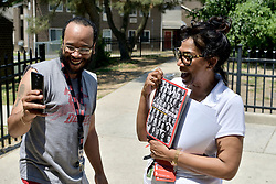 Tanzie Youngblood holds up a Time cover that features the candidate as Will Brant holds up his phone to record a Snapchat story, at a low-income housing project in Bridgeton,  NJ, on May 26, 2018.