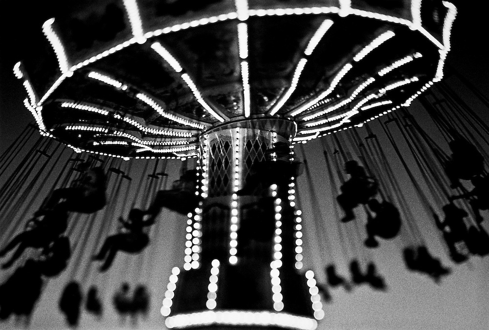 Black and white selective focus night shot of people on a county fair carousel swing.