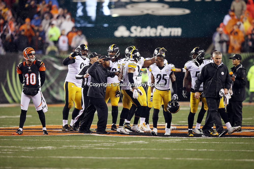 A Pittsburgh Steelers coach and NFL line judge Ron Marinucci (107) try to regain order and clear the field of unnecessary players and coaches after Cincinnati Bengals running back Giovani Bernard (25) gets hit hard by Pittsburgh Steelers inside linebacker Ryan Shazier (50) causing a third quarter fumble, recovered by Shazier, and starting a player melee over no penalty call for unnecessary roughness and leading with the helmet during the NFL AFC Wild Card playoff football game against the Pittsburgh Steelers on Saturday, Jan. 9, 2016 in Cincinnati. The Steelers won the game 18-16. (©Paul Anthony Spinelli)