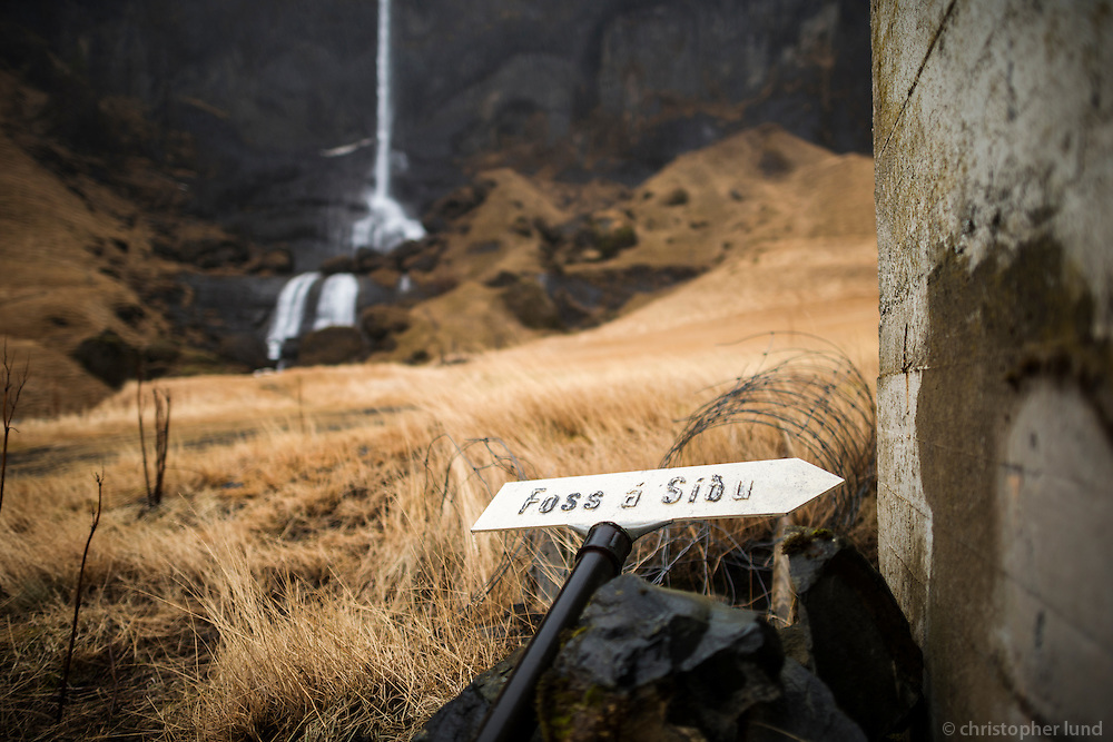 The old sign for the farm Foss á Síðu lies on the ground, by one of the older houses. The waterfall (also called Foss á Síðu) in background. The water comes from a lake called Þórutjörn.
