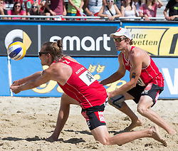 30.07.2014, Strandbad, Klagenfurt, AUT, FIVT, A1 Beachvolleyball Grand Slam 2014, Hauptrunde, im Bild Daniel Müllner (AUT) und Jörg Wutzl (AUT, hinten) // during Main Draw Match of the A1 Beachvolleyball Grand Slam at the Strandbad Klagenfurt, Austria on 2014/07/30. EXPA Pictures © 2014, EXPA Pictures © 2014, PhotoCredit: EXPA/ Johann Groder