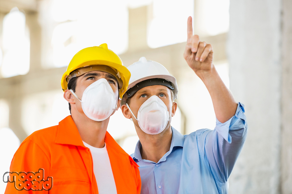 Male architects wearing protective mask while working at construction site